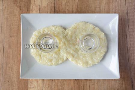 На большое квадратное или круглое блюдо, на незначительном расстоянии друг от друга, ставим 2 бокала или рюмки. Вокруг этих стаканов выкладываем первым слоем тёртый картофель с майонезом, в виде цифры 8.