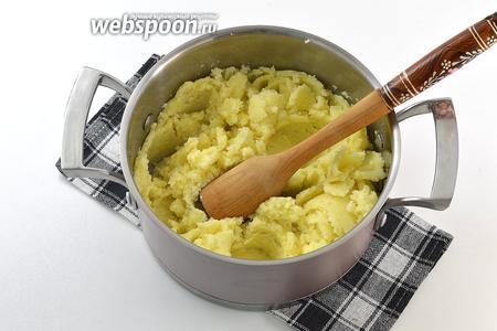 Если картофель готов — всю воду слить. Тщательно размять горячий картофель с помощью толкушки.