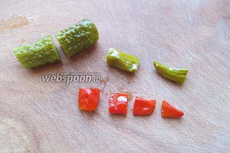 Нарезаем огурцы и перцы. Огурцы — пополам, красные перцы (4 штуки) — на 4 части, зелёные перцы (8 штук) —  на 2 части.