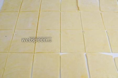 Тесто вынуть из холодильника. Раскатать тонко в форме прямоугольника. Разрезать на куски в размере 7Х8 см.
