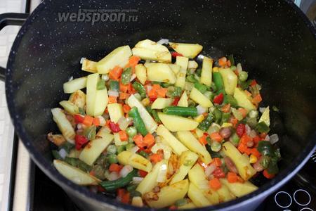 Добавить овощную смесь, всё перемешать, чуть пожарить и добавить воды (0,5 стакана), накрыть крышкой, убавить огонь и тушить до готовности овощей.