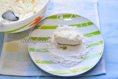 Пару столовых ложек муки насыплем в тарелку. Столовой ложкой и мокрыми руками формуем сырники и обваливаем их в муке.