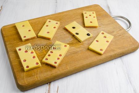 Собираем бутерброд: слой-основа, слой-колбаса, слой-сыр с отверстиями. С помощью той же вырубки нарезать кусочки чернослива и заполнить отверстия (в крайнем случае можно оставить без заполнения).