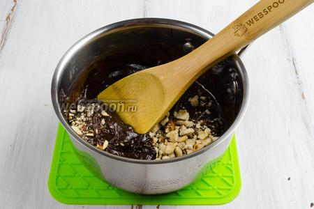 Добавить к шоколадной массе подготовленные орехи. Перемешать.