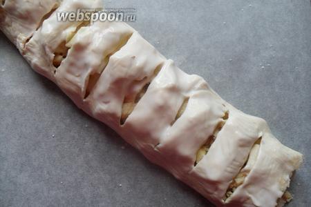 Аккуратно сворачиваем тесто с начинкой в рулет, делаем неглубокие надрезы и смазываем сверху кефиром или молоком.