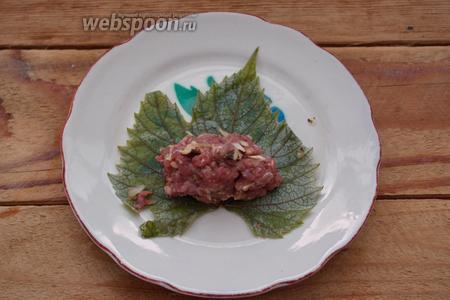 На листик винограда выкладываем котлетку из подготовленного фарша. Сверните листик в конвертик, заключив мясо внутри.