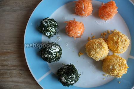 Шарики с арахисом выкатываем в укропе, другие, с белком, — в желтке, третьи — в морковке. Вот такая лёгкая закуска. Насаживаем на шпажку, формируем канапе.
