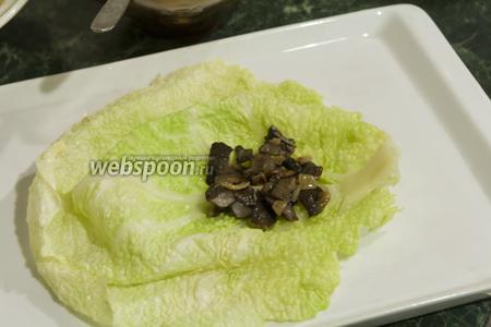 Если у вас толстые листы в капусте, то отбейте их. Нам досталась капуста с тоненькими листочками, поэтому мы обойдёмся без отбивания. Выкладываем по полной столовой ложке грибного фарша на каждый подготовленный лист.
