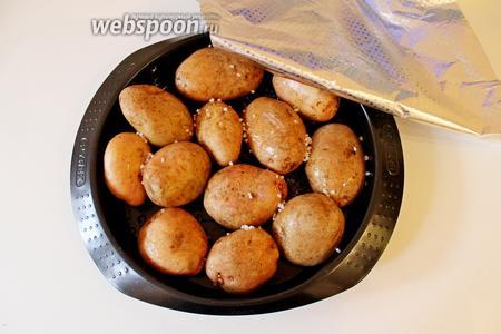 Картофель хорошо промыть щёткой, обсушить и выложить в форму, полить оливковым маслом и присыпать морской солью, накрыть плотно форму фольгой и запекать картофель при 200°С 45-60 минут, в зависимости от размера картофеля.