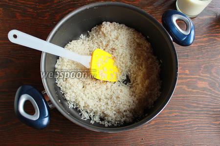 Вернуть кастрюлю на огонь, всыпать рис и оставшейся сахар, перемешать.