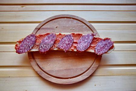 Сверху выложим кусочки тонко-нарезанной сырокопчёной колбасы. Будет здорово, если она окажется чуть островатой!