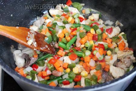 Добавить к обжаренному мясу с луком овощную смесь, тушить под крышкой 10 минут.