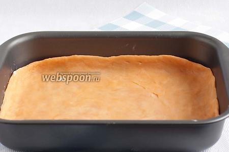 Тесто достать из холодильника и разделить на 2 части. Каждую часть раскатать по размеру своей формы. На дно формы выложить 1 пласт теста.