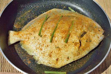 Сделайте 2-3 надреза и в эти прорези положите по 1 кусочку зелёного лука. Посолите и посыпьте немного специями рыбу с 2 сторон.