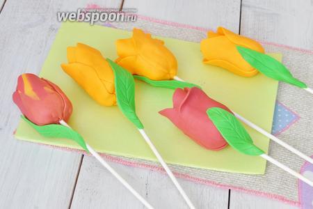 Так же формируем и красные тюльпаны. Если красную мастику соединить с жёлтой и не перемешивать до полного поглощения цвета, а сразу раскатывать, то получим красный тюльпан с жёлтыми разводами. Клеим на воду к палочкам и бутонам листья и наш букет готов.