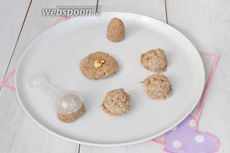 Отмеряя смесь мерной ложкой (объём 1 столовая ложка), выкладывать заготовки на блюдо. Формировать шарик. Прижать его ладонями. Положить в центр орех. Сформировать кейк попс в форме бутона цветка.