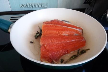 Кусок рыбы разрезаем по хребтовой кости. Сковороду разогреем с небольшим количеством растительного масла, кладём на неё веточку розмарина, горошины перца и, немного погодя, рыбу кожицей вниз.