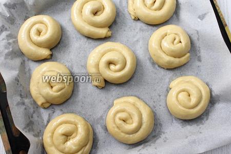 Выкладываем булочки на противень, застеленный бумагой для выпечки. Смазываем их слегка растопленным сливочным маслом. Даём булочкам расстояться перед выпечкой 15-20 минут.
