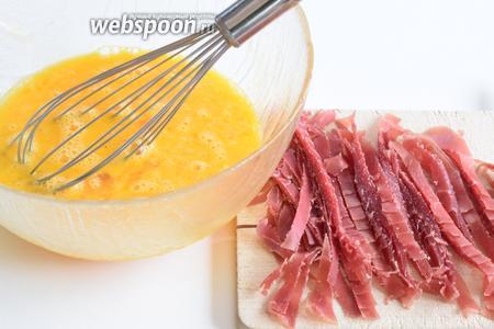 Яйца немного взбиваем венчиком, подсолим и поперчим. Мясо нарезаем полосками.