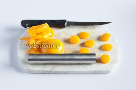С помощью маленькой круглой контурной формы вырезаем из консервированных персиков цилиндрики — это будут желтки. Я пользуюсь приспособой для вырезания сердцевин яблок. Персики толстые, а желтки нам потребуются достаточно тонкие, так что лучше разрезать их на половинки ножом. Гладкие верхние части (которые были у персиков под шкуркой) откладываем, они нам нужны для декора. Количество желтков должно совпадать с количеством половинок шоколадных яиц.