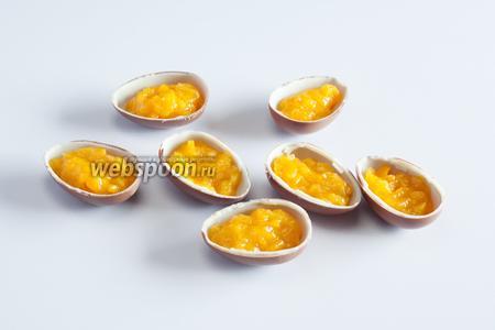 Выкладываем персиковое пюре в половинки шоколадных яиц — где-то по 1 столовой ложке.