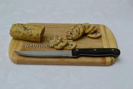 Вынуть тесто из морозилки, освободить от плёнки и нарезать очень острым ножом на кружочки, толщиной 3-4 мм.