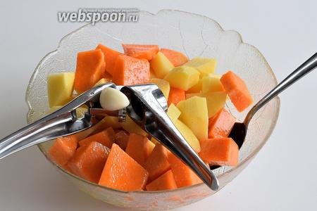 Этим временем подготовим картофель и тыкву. Почистим и нарежем на кубики. Приправим оливковым маслом и солью. Выжмем через пресс зубок чеснока и всё вместе перемешаем.