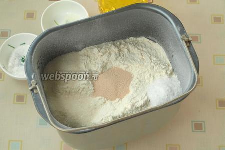 Сверху просеять муку, по углам насыпать соль и сахар. В центре сделать углубление и всыпать дрожжи.