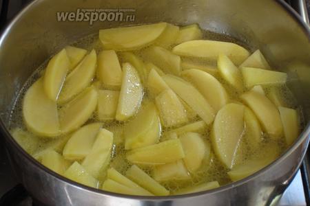 В большую кастрюлю влить оставшееся оливковое масло, выложить картофель, поставить на средний огонь и влить горячую воду или овощной бульон. Готовить 5 минут.