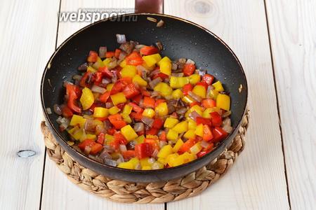 Добавьте к луку сладкий перец, обжаривайте всё вместе 1-2 минуты, помешивая.