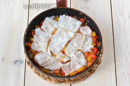 Филе хека выньте из маринада, нарежьте и выложите на подушку из овощей. Лёгким нажатием немного «утопите» рыбу. Если на филе остались кусочки чеснока, не убирайте их. Добавьте 2 ст. л. маринада.