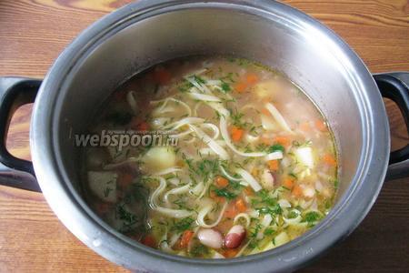 В готовый суп с фасолью и лапшой кладём нарезанную зелень. Густоту супа регулируйте по своему вкусу.