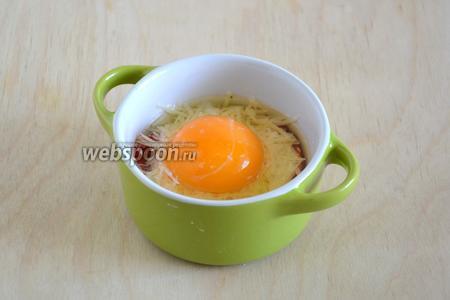 Выпустите в каждую кокотницу по 1 яйцу. Старайтесь сохранить желток целым. Ещё немного посолите.