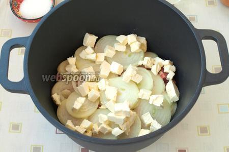 Кусочками нарезать сливочное масло и разместить его поверх лука. Казан накрыть крышкой и томить мясо 1 час на медленном огне, не открывая крышку.