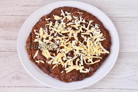 На печёночный корж с кунжутными семечками кладём натёртый сыр.