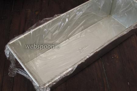 Прямоугольную форму для кекса выстелить пищевой плёнкой.