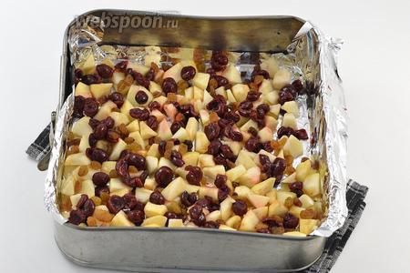 Форму размером 20х20 см выложить кулинарной бумагой или фольгой. Смазать подсолнечным маслом. На дно выложить очищенные и нарезанные кубиком яблоки, вишню без сиропа, промытый изюм.