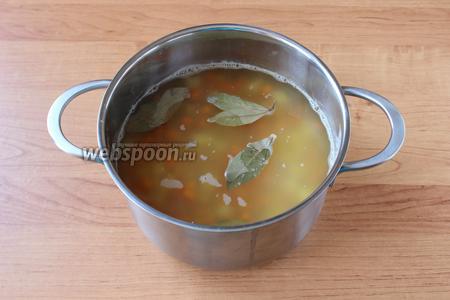 Спустя час, добавить к гороху картофель, морковь, бульон, лавровый лист и варить в течение 20 минут.