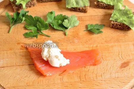 Рыбу нарезать на длинные ломтики, но неширокие. Ширина должна быть примерно размером равной стороне хлебного квадратика. На ломтик сёмги положить примерно 1 чайную ложку сыра.