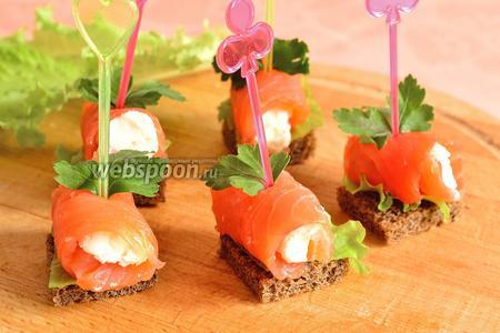 Рулетик из рыбы положить на кусочек хлеба с салатным листом. Сверху воткнуть листик петрушки и шпажку для канапе. Канапе из сёмги с творожным сыром готовы.
