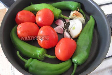 Выкладываем на сухую сковороду помидоры, зелёный перец, неочищенные лук и чеснок.
