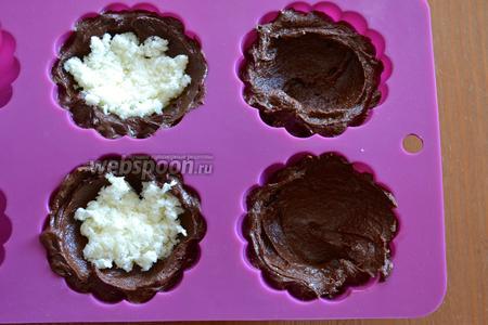 Силиконовые формочки заполнить шоколадным тестом, выложив его по краям и на дно формочек. В центр выложить часть кокосовой начинки. Осторожно всё утрамбовываем.