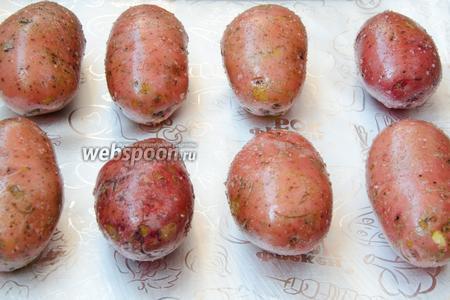 Выложить картофель на противень, застеленный фольгой. Отправить его в разогретую до 220°С духовку и выпекать в течение 50-60 минут. Через 30 минут после начала запекания, картофель необходимо перевернуть, чтобы он равномерно пропёкся с обеих сторон.