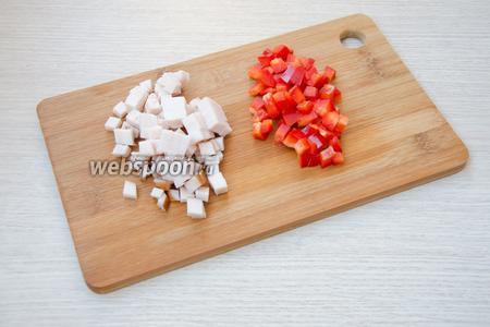 Пока картофель остывает, можно заняться начинкой. Для этого куриное филе необходимо порезать кубиками небольшого размера. Из перца удалить сердцевину и также порезать его небольшими кубиками.