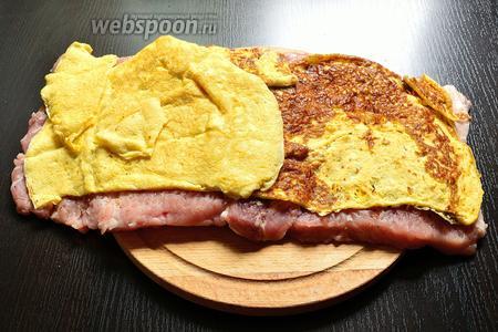 Яичные блинчики выложить на отбитый кусок свинины, так, чтобы он покрыл практически весь кусок. 1 край оставляю свободным на 1-2 см от блина.