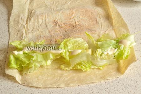 На край лаваша положить листья айсберга. Айсберг я просто рву руками. На салат выдавить немного майонеза.