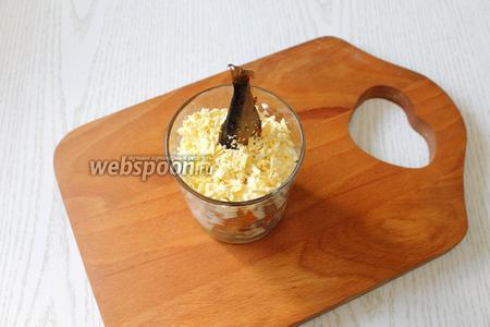 Вставляем в салат вертикально шпротину, посыпаем желтками, потертыми через мелкую тёрку.