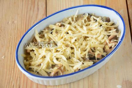 Посыпаем кальмары тёртым сыром. Запекаем в разогретой до 180-200°С духовке, 5-10 минут, до полного расплавления сыра.