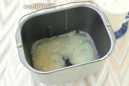 В контейнер хлебопечки влить молочную сыворотку и добавить растопленный смалец. Сыворотку также можно подогреть, тогда смалец не возьмётся кусочками, хотя при замесе это не играет никакой роли.