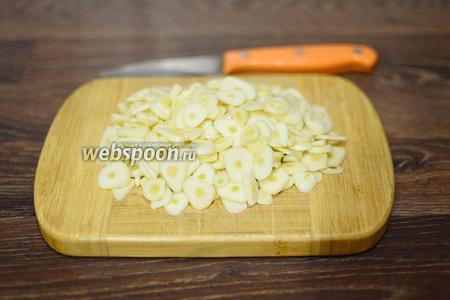 Нарезаем весь чеснок тонкими одинаковыми пластинами.